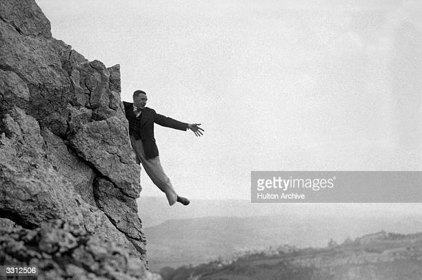 A climber on the Little Orme at Llandudno North Wales balancing on one leg as he tries to reach his hat which had been blown off his head