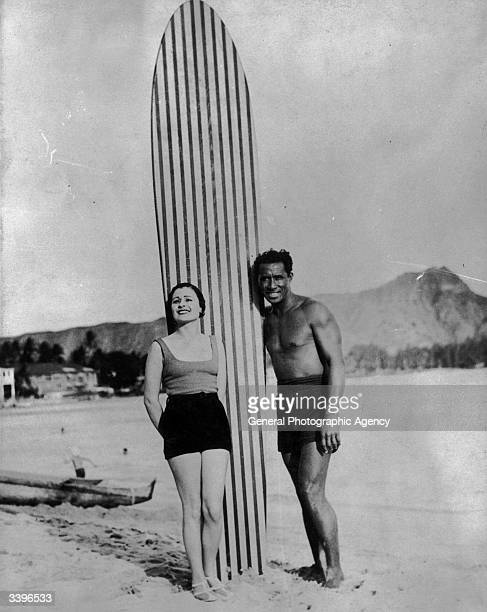 A couple with a large striped surfboard The man is Olympic swimming champion and pioneer surfer Duke Kahanamoku a Hawaiian hero