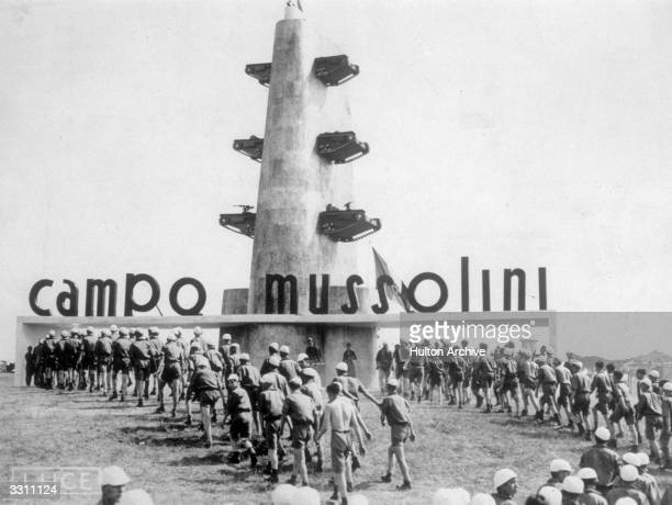 A crowd of boys seen here climbing up to the entrance of Camp Mussolini at Monte Sacro Note the tanks attached to the pylon which guards the entrance...