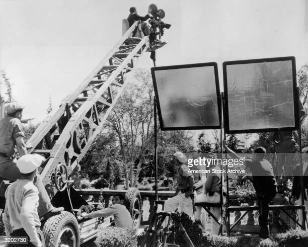 A director and a cameraman sit on a crane with a motion picture camera while filming outdoors on a movie set Two light reflectors are angled at the...