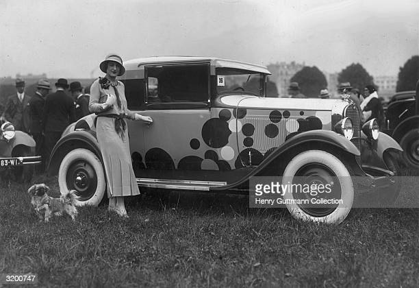 A fashionably dressed woman in a dress by Mlle Eigrane stands with her dog by a Citroen car which has whitewalled tyres and is painted with random...