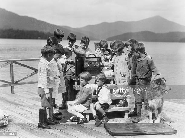 A group of children and a collie dog listen to a portable radio on some wooden steps on a dock on a mountain lake Australia
