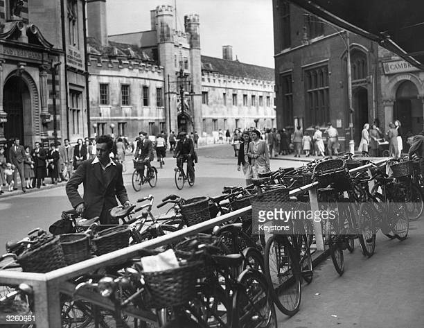 Large number of bicycles lean against a railing in Cambridge.