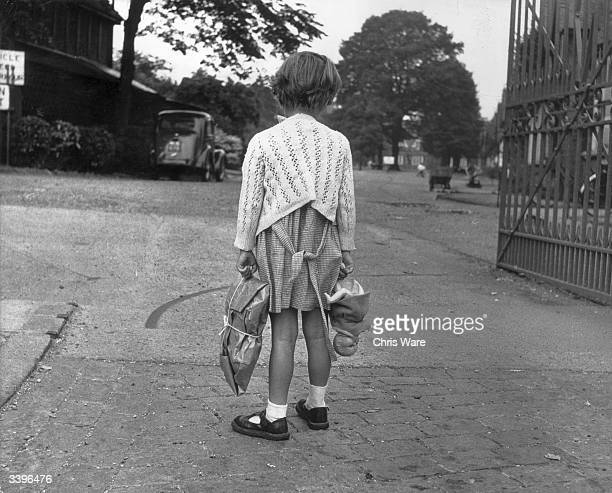 Lonely child holding her possessions outside the gates of a housing estate.