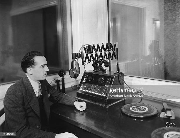 A man sits at a desk with a telephone a turntable a microphone and a machine with volume controls inside a radio studio 1930s
