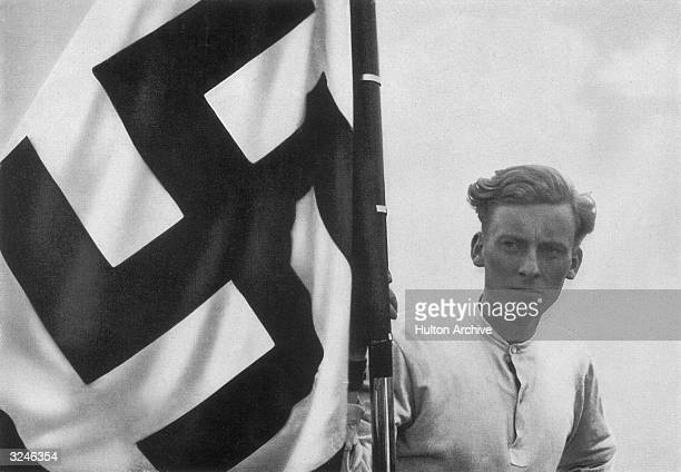 Member of the Hitler Youth with a swastika flag at a Nazi rally in Germany. Original Publication: From a series of collectable images published in...