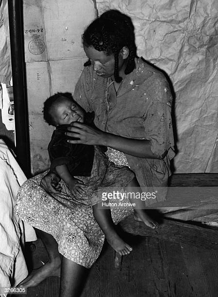 A migrant strawberry picker with her baby in a cardboard shack in Louisiana