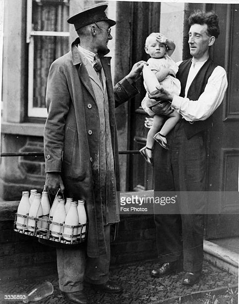 A milkman chats with a father holding a baby as he leaves the daily quota of milk on the doorstep