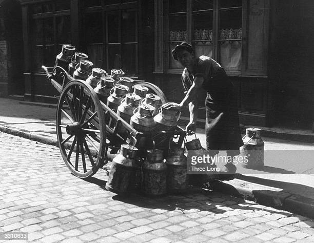 A milkman delivering milk in churns with his cart