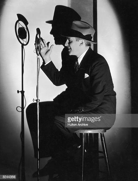 A profile portrait of American journalist Walter Winchell waving his hand in front of a microphone with his shadow cast on the wall behind him