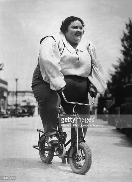 Rather large woman riding a mini-autobike.Tiny Griffin preparing to take part in a South California Bicycle Parade at Ocean Park.
