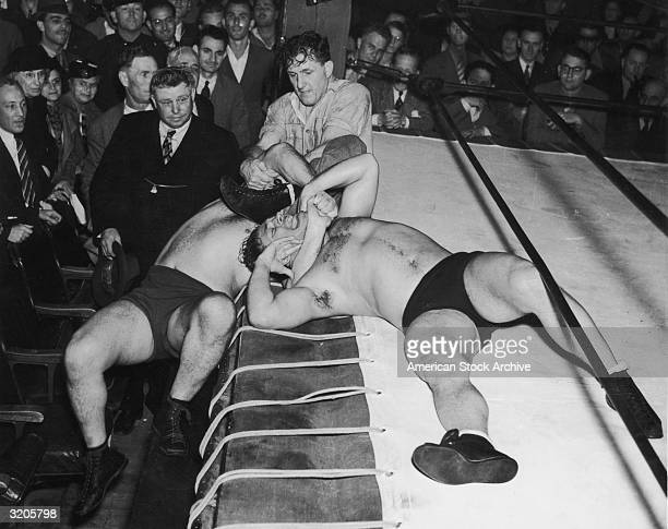 A referee tries to pull apart two wrestlers struggling outside of the ring one of whom has a headlock on the other during a professional match
