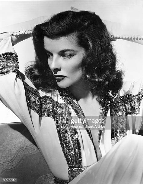 A studio portrait of American actress Katharine Hepburn sitting with her arms behind her head and looking to the side She is wearing a white blouse...