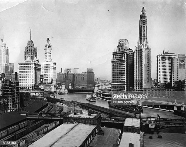 A view of Chicago with the Chicago River dividing it The Wrigley Building with the clock is on the left and the Nather Building with the high tower...
