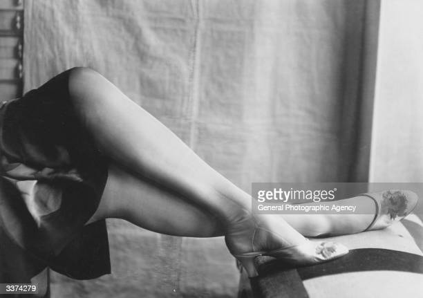 Woman modelling a pair of embroidered silver slippers designed by Perugia.