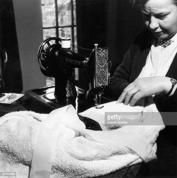 A woman using a Singer sewing machine to sew ribbon on to towelling material Farmers Weekly Household Hints