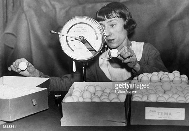 Woman weighing table tennis balls at the Jacques factory, London.