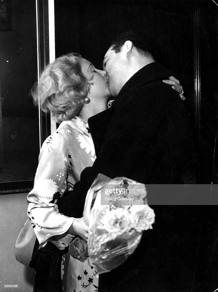 A young couple kissing whilst wearing evening dress  News