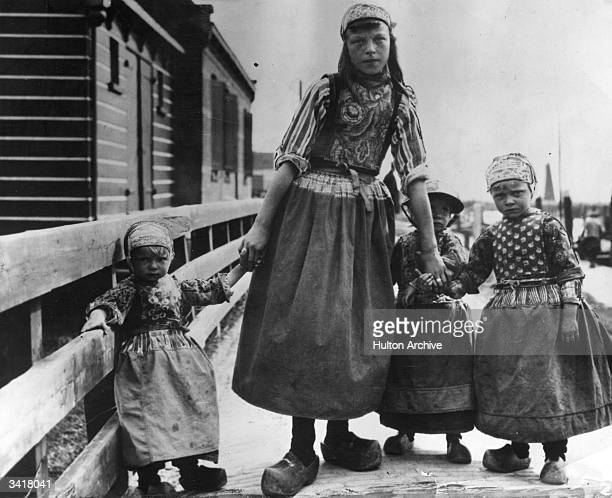 A young Dutch mother with her children in their national costume including clogs