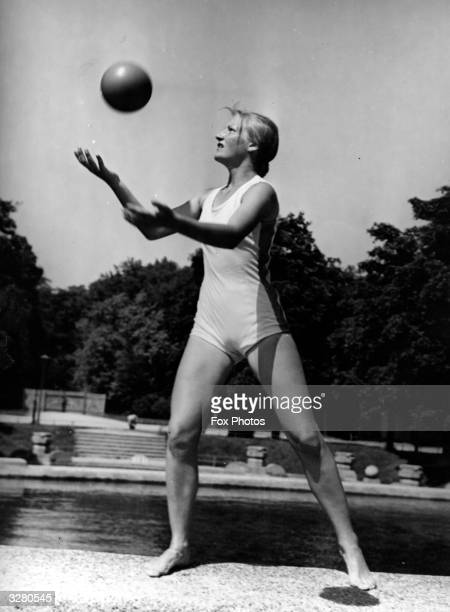 Young female member of Hitler Youth plays with a ball in the sunshine.