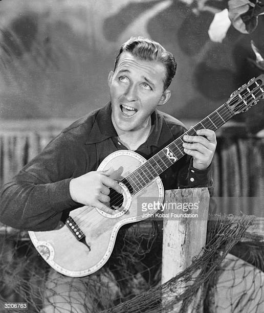 Actor and singer Bing Crosby strums a happy tune on his guitar