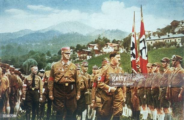 Adolf Hitler inspects a regiment of troops carrying swastikas