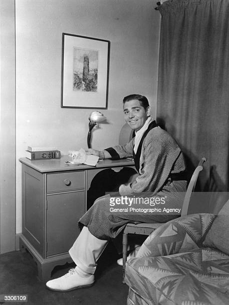 American actor Clark Gable star of 'Gone With The Wind' reading a letter in his dressing room