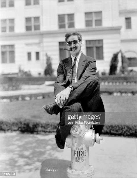 American actor Groucho Marx perches on a fire hydrant