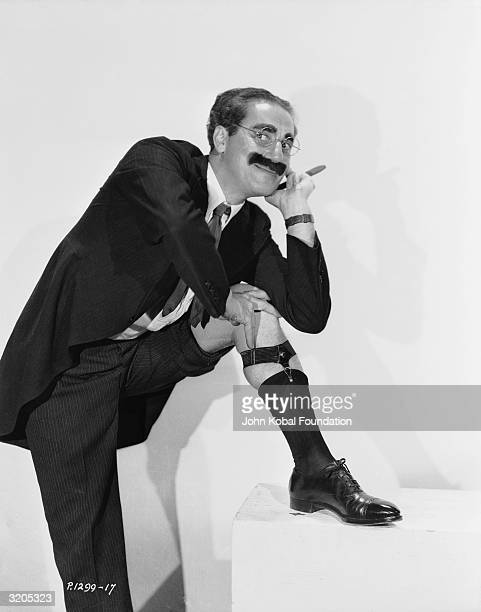 American actor Groucho Marx pulls up one trouser leg to reveal his suspender