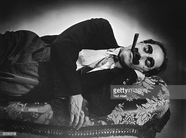 American actor Groucho Marx sleeps on a couch with a cigar still clamped between his lips