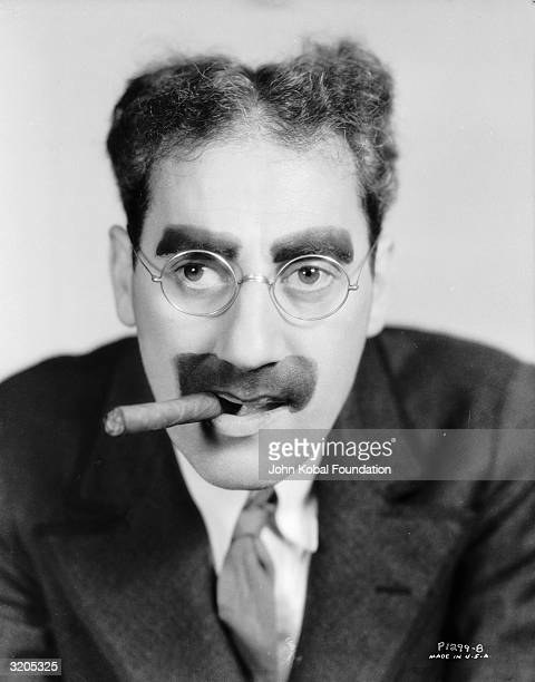 American actor Groucho Marx with his trademark moustache and glasses