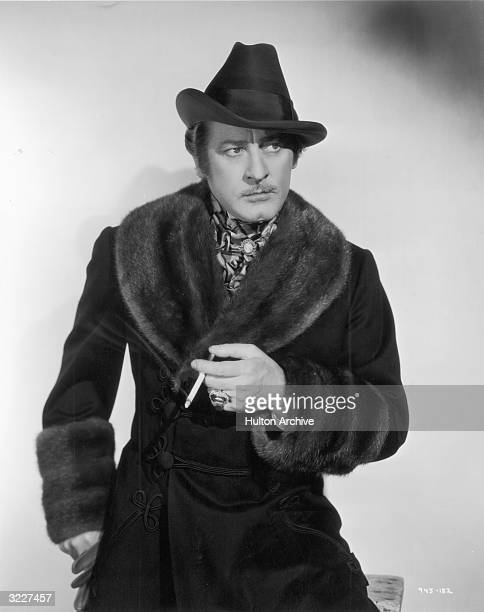 American actor John Barrymore holds a cigarette while wearing a costume consisting of a hat an ascot and a dark coat with a fur collar and cuffs in a...
