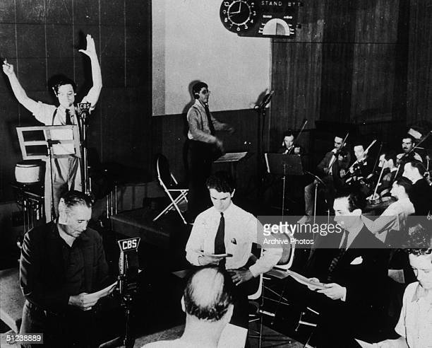 Circa 1935 American actor writer producer and director Orson Welles standing in front of a microphone with his arms raised above his head while the...