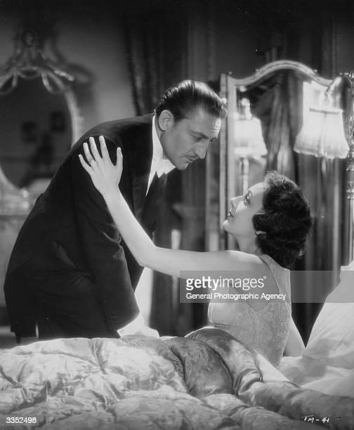American actors Warren William and Ann Dvorak share a romantic moment in the film 'The Return of Arsene Lupin'