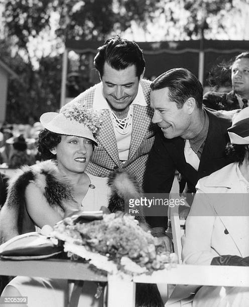 American actress Gloria Swanson receives the attentions of actors Johnny Mack Brown and Joe E Brown at an Uplifters charity polo game
