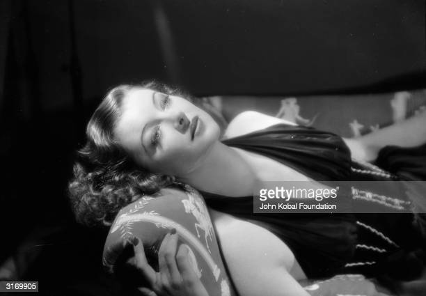 American actress Myrna Loy reclining on a sofa