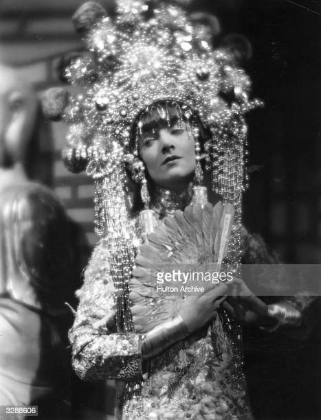 American actress Myrna Loy wearing an elaborate Balinese costume in a scene from an unknown film