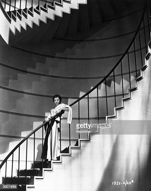 American actress Sylvia Sidney standing on a spiral staircase.