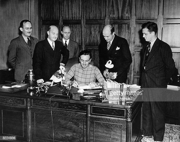 American animator and producer Walt Disney is surrounded by a group of executives while seated at his desk in his office Donald Duck and Mickey Mouse...