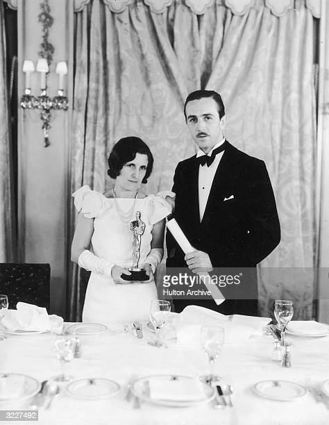 American animator and producer Walt Disney stands next to his wife Lillian Bounds who is holding one of Disney's Oscars possibly at an Academy Awards...