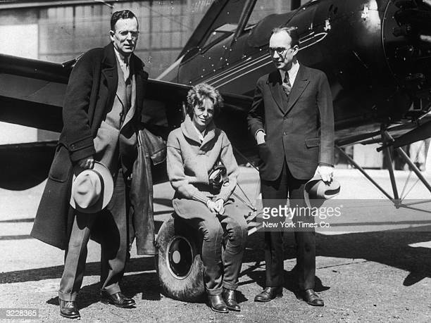 American aviator Amelia Earhart sits on the wheel of an airplane between her husband, publisher, George Palmer Putnam and airplane designer Harold...