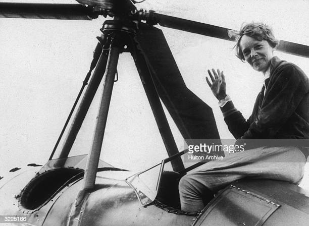 American aviator Amelia Earhart the first woman to complete a solo transatlantic flight waves as she emerges from the cockpit of a rotorcraft Newark...