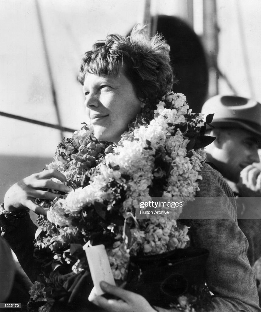 American aviator Amelia Earhart (1898 - 1937), the first woman to fly solo across the Atlantic, decorated with leis during her visit to Honolulu, Hawaii. Earhart had arrived by ship.