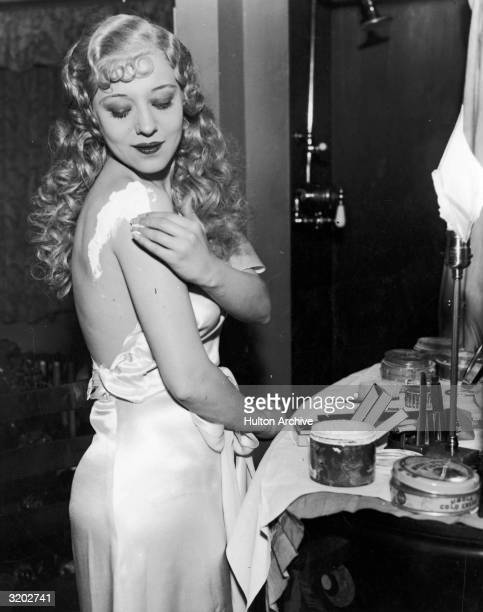 American burlesque dancer Sally Rand applies grease paint to her shoulder in preparation for her fan and bubble dance Rand first performed her fan...