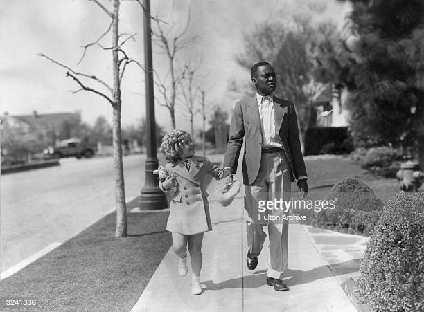 American child actor Shirley Temple holds hands with actor tap dancer Bill 'Bojangles' Robinson while walking on a sidewalk at 20th CenturyFox...