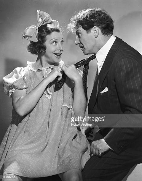 American comedian Fanny Brice dressed as her young girl persona Baby Snooks pulls British actor Hanley Stafford's tie in a promotional portrait for...
