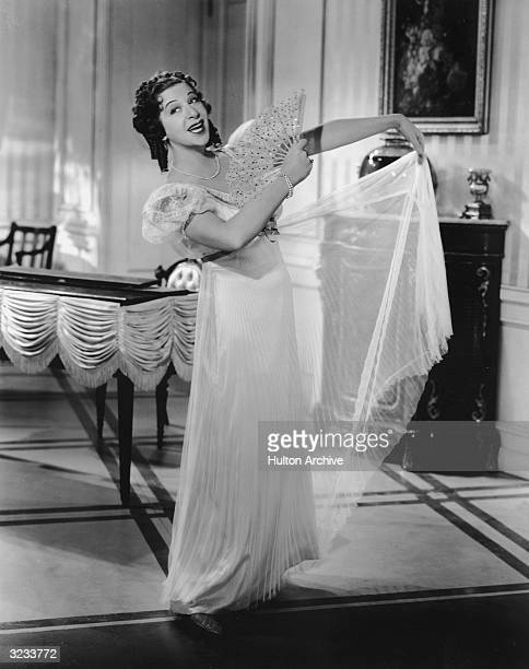 American comedian Fanny Brice sings while fanning herself in a dress with an Empirewaist in an unidentified film still