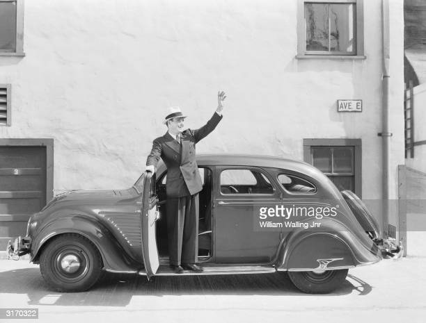 American film actor,, and former Olympic swimming champion, Larry 'Buster' Crabbe waves from the running board of his car.