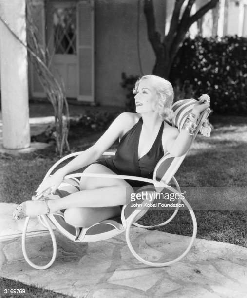 American film actress Carole Lombard lounging on a garden chair