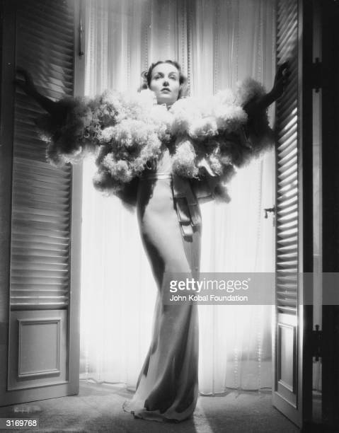 American film actress Carole Lombard stands framed by a doorway